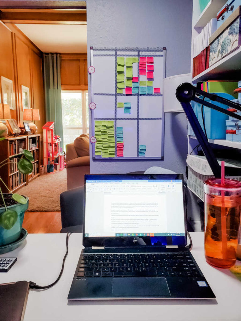 laptop on desk with kanban board on wall in background