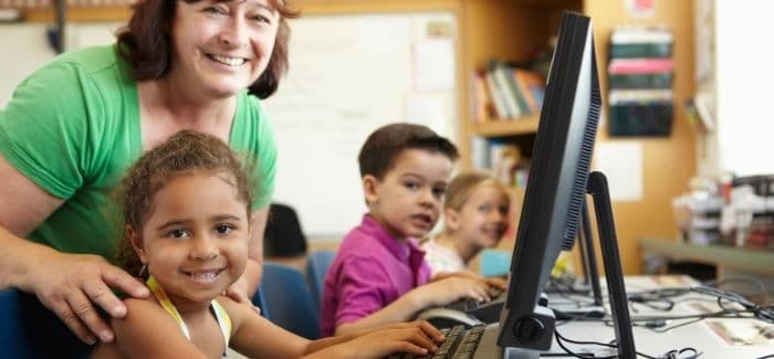 teacher leaning over student at computer