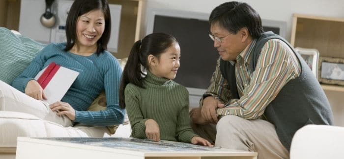 mother, father, and daughter talking in living room