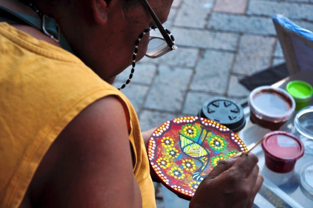 aboriginal woman doing dot painting